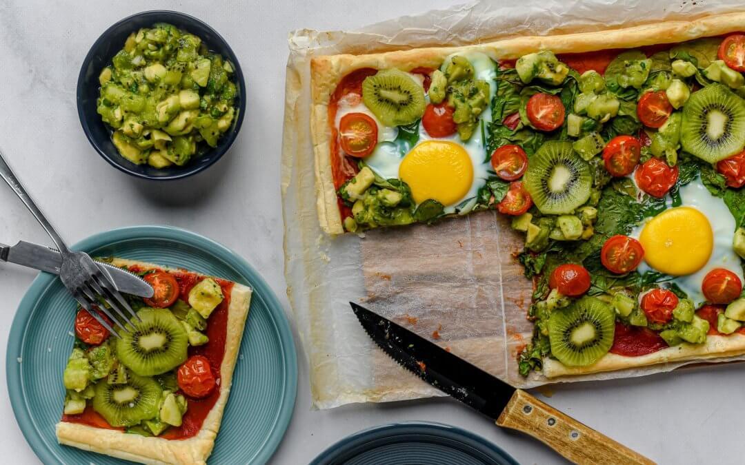 Ontbijtpizza met spiegelei, spinazie, cherrytomaatjes en avocado-kiwisalsa
